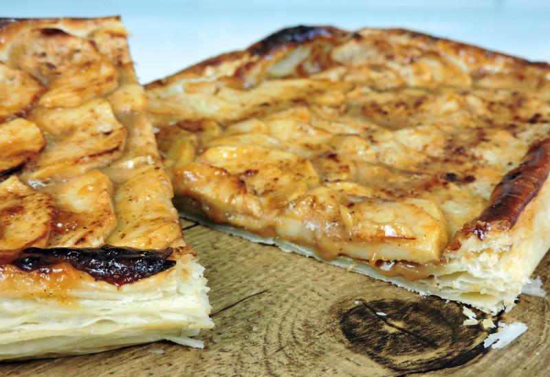 Corte de la tarta de manzana, hojaldre y dulce de leche