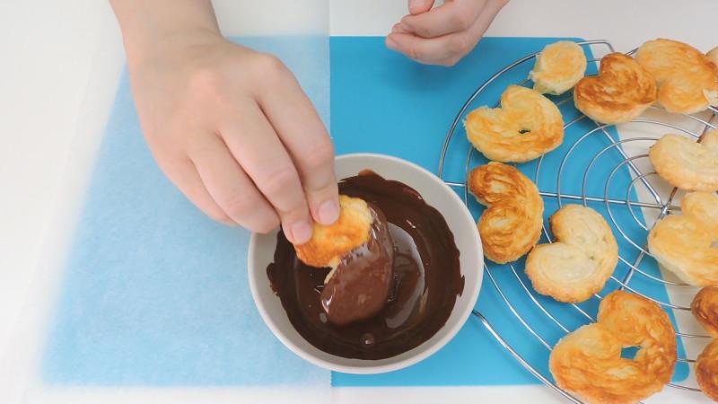Mojando las palmeritas horneadas en chocolate