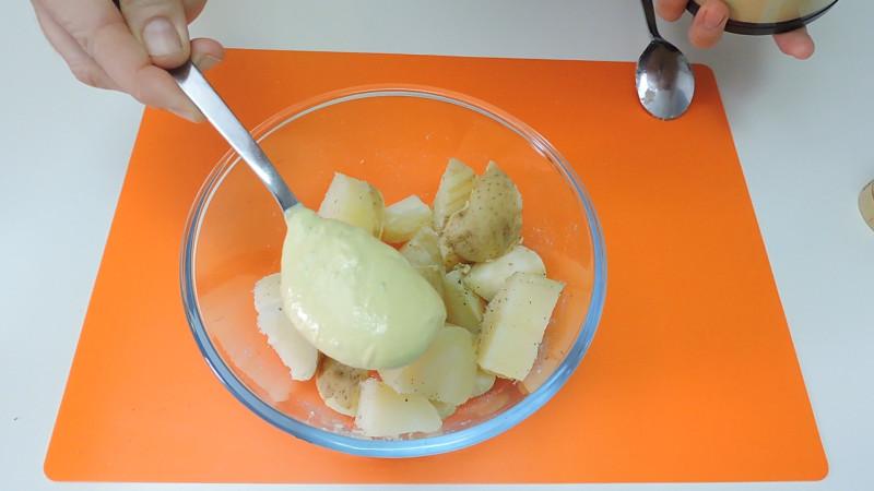 Poniendo el alioli sobre las patatas cocidas