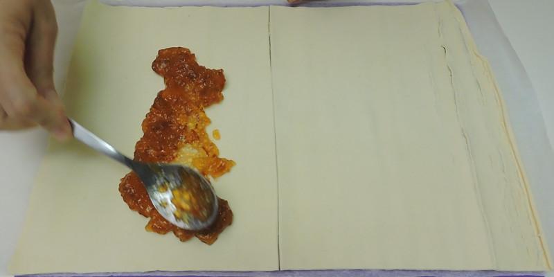 Poniendo la mermelada de naranja sobre el hojaldre
