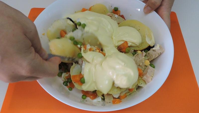Añadiendo la salsa mayonesa a la ensaladilla rusa