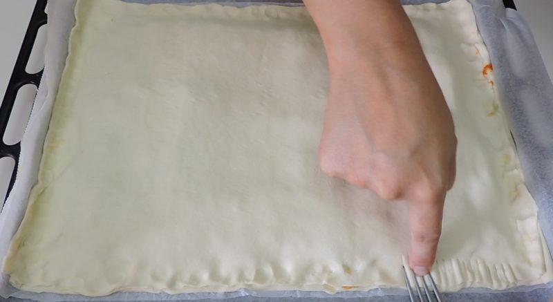 Sellando los bordes de la empanada de hojaldre con un tenedor