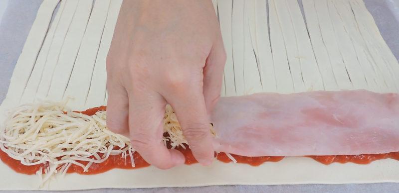 Poniendo el jamón y el queso sobre el hojaldre