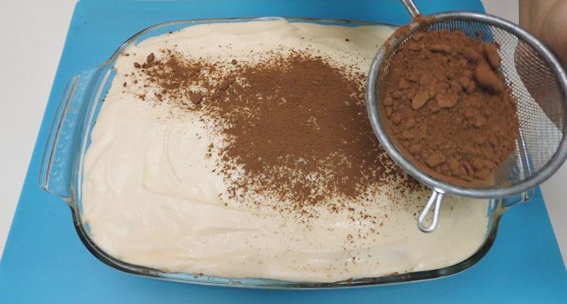 Espolvoreando cacao sobre el tiramisú