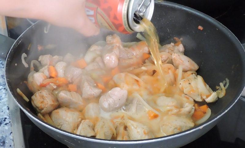 Añadiendo la cerveza al guiso de carne y verduras