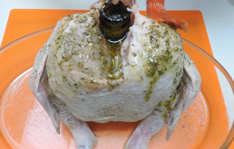 Untando la mezcla de hiervas y aceite sobre la piel del pollo