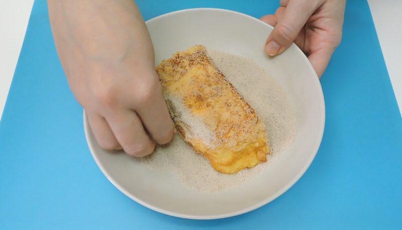 Rebozando la torrija frita en azúcar y canela