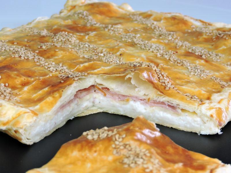 Empanada de hojaldre rellena de jamón, queso y bechamel