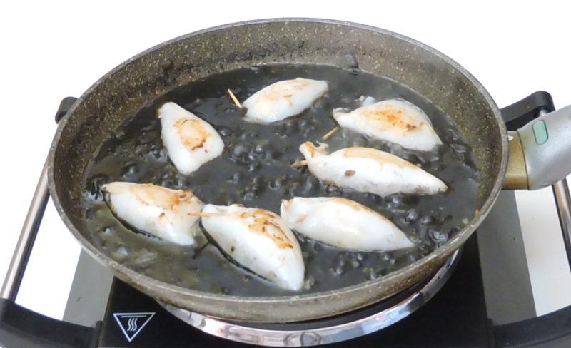 Chipirones cocinándose en la salsa de tinta