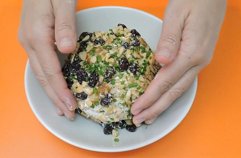Cubriendo la bola de queso con la mezcla de frutos secos y cebollino