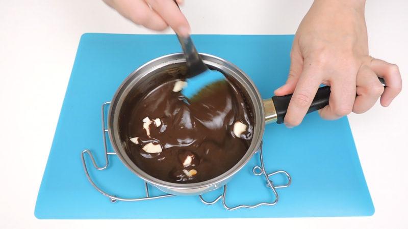 Integrando la mantequilla en la mezcla de nata y chocolate