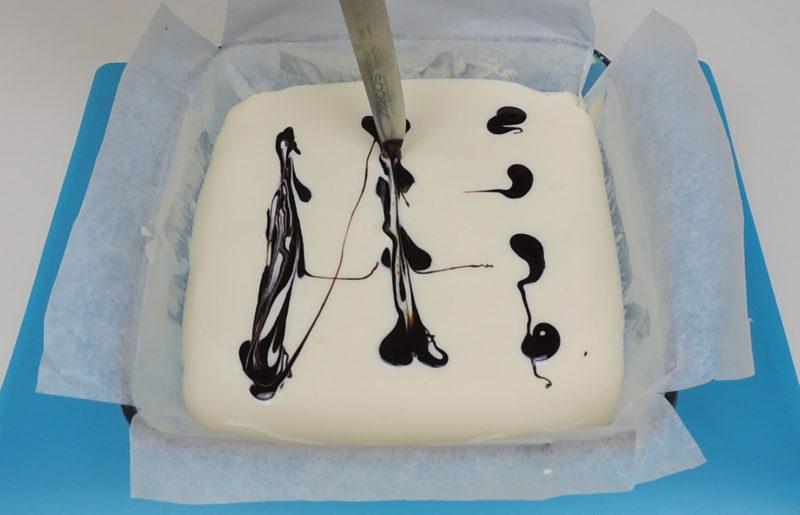 Decorando la capa de queso con sirope de chocolate