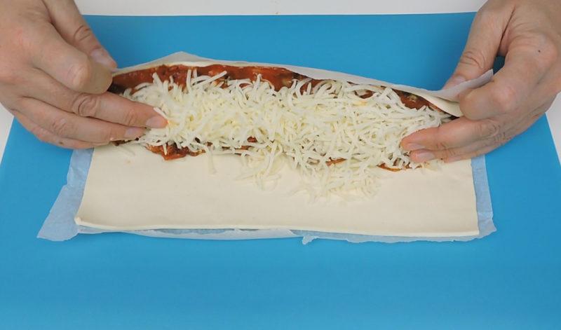 Enrollando el hojaldre relleno con sabor a pizza