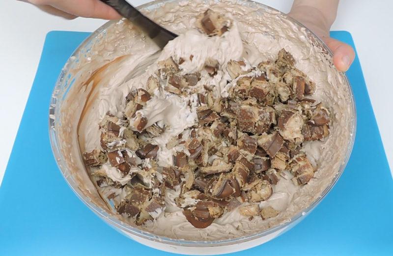 Integrando los trozos de Kinder Bueno en la mezcla de queso, chocolate y nata