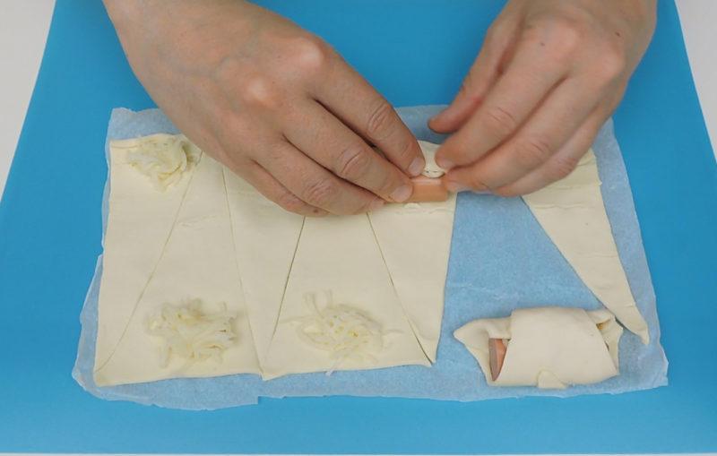Enrollando el triángulo de hojaldre relleno de salchicha y queso