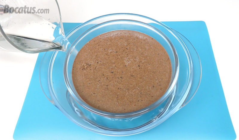 Poniendo agua caliente en un recipiente para hornear el flan al baño María