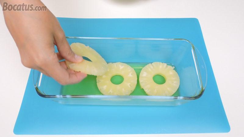 Colocando las rodajas de piña sobre la gelatina solidificada