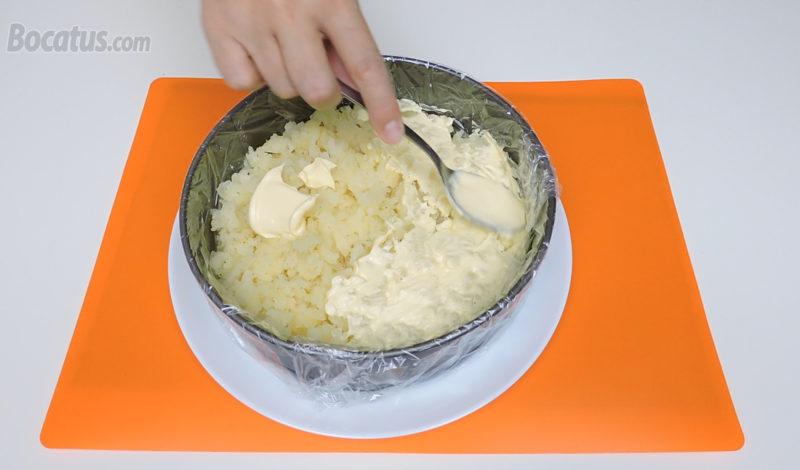 Extendiendo mayonesa sobre la capa de patata