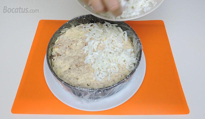 Poniendo la clara de huevo sobre la capa de atún y mayonesa
