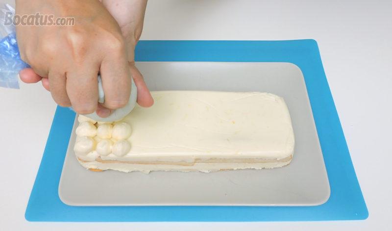 Poniendo copetes de crema de limón y queso en la superficie del tiramisú