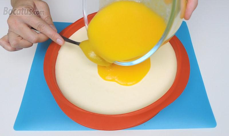 Vertiendo el puré de mango en la superficie de la tarta