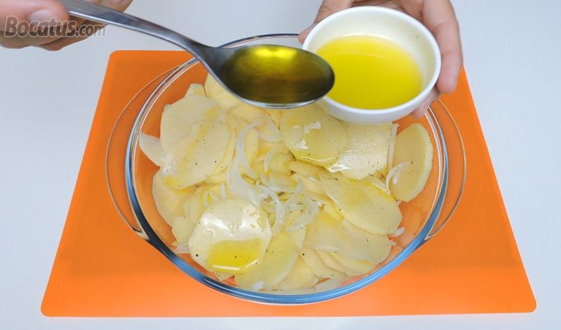 Añadiendo el aceite a las patatas y a la cebolla