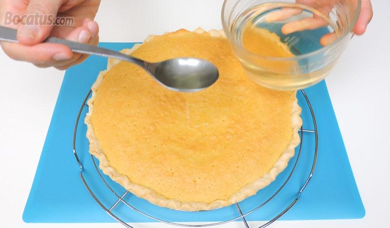 Calando la tarta de almendra con el almíbar