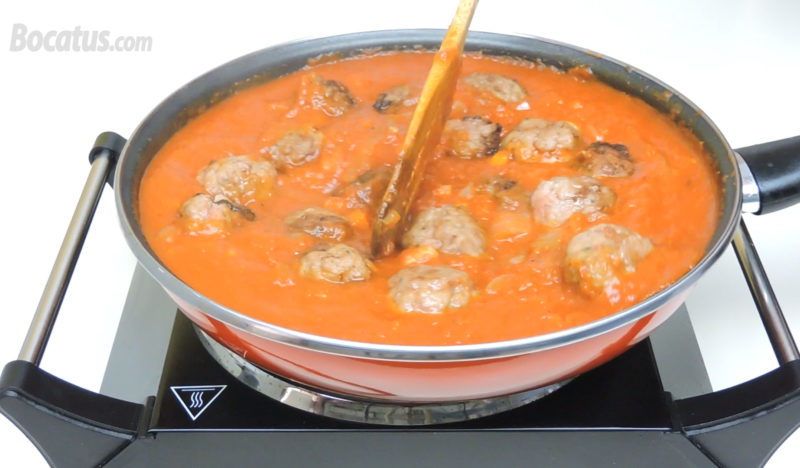 Cocinando las albóndigas en la salsa de tomate
