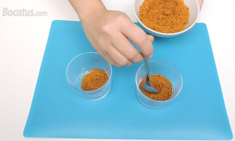 Poniendo las galletas trituradas en los vasitos
