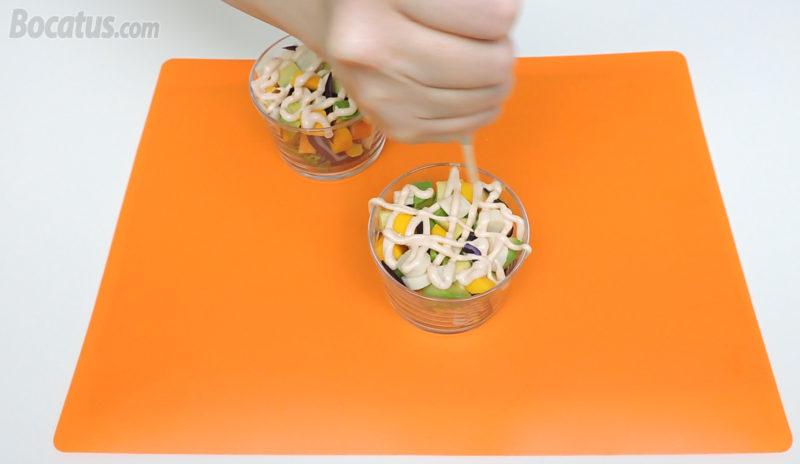 Añadiendo la salsa rosa en la superficie de la ensalada