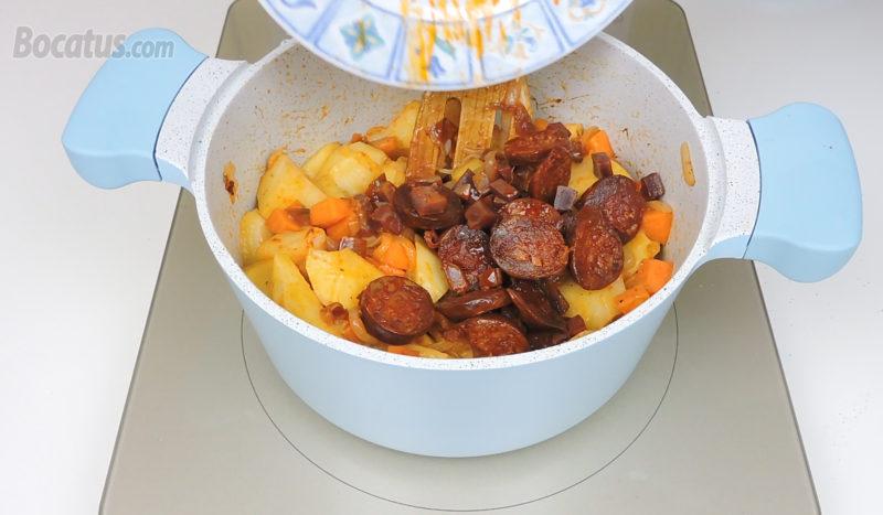 Añadiendo el chorizo y el jamón a la olla
