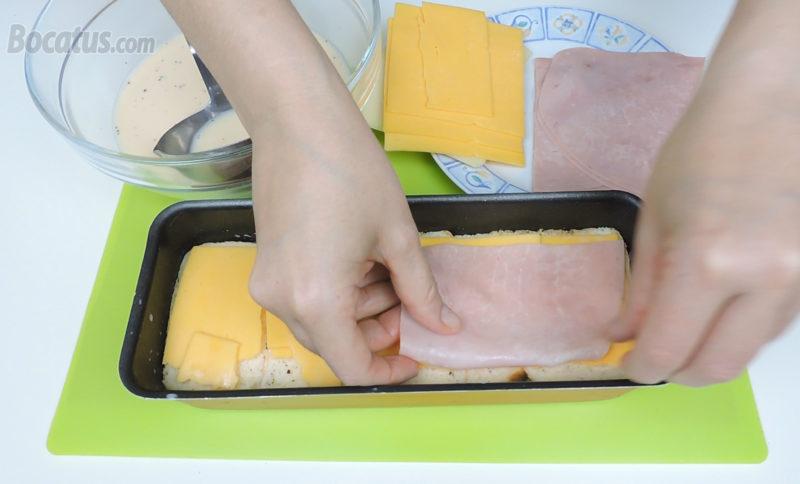 Poniendo la capa de queso Cheddar y jamón
