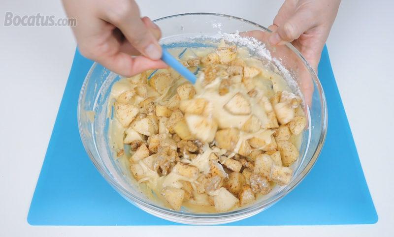 Integrando la mezcla de manzanas y nueces en la masa de bizcocho