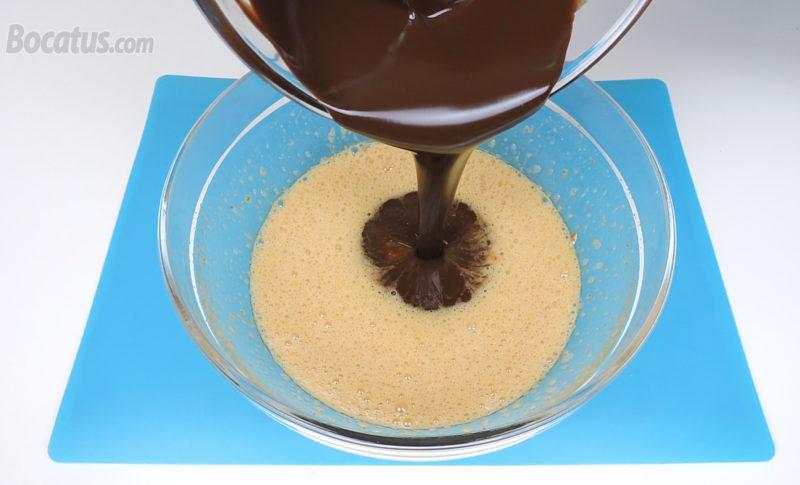 Vertiendo la mezcla de chocolate y mantequilla sobre la mezcla de huevos y azúcar