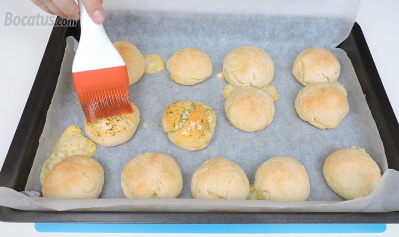 Pincelando los panecillos recién horneados con la salsa de ajo