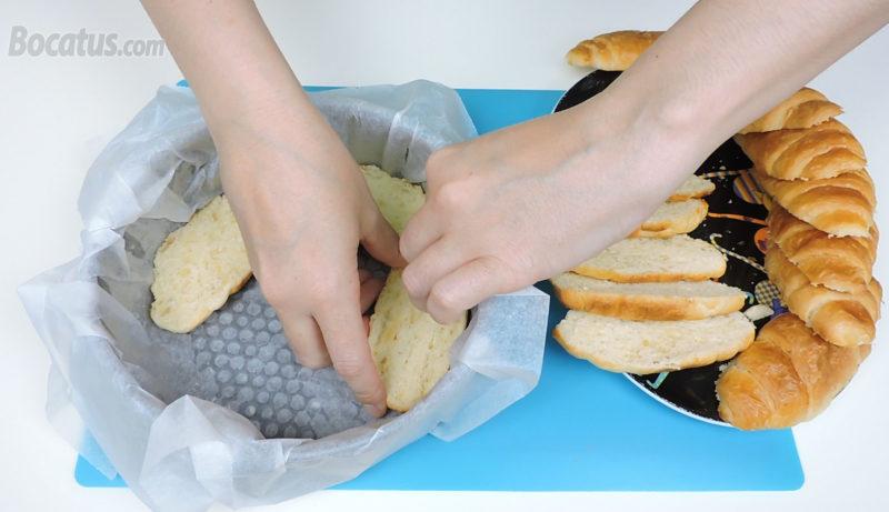 Colocando la primera capa de cruasanes en el molde