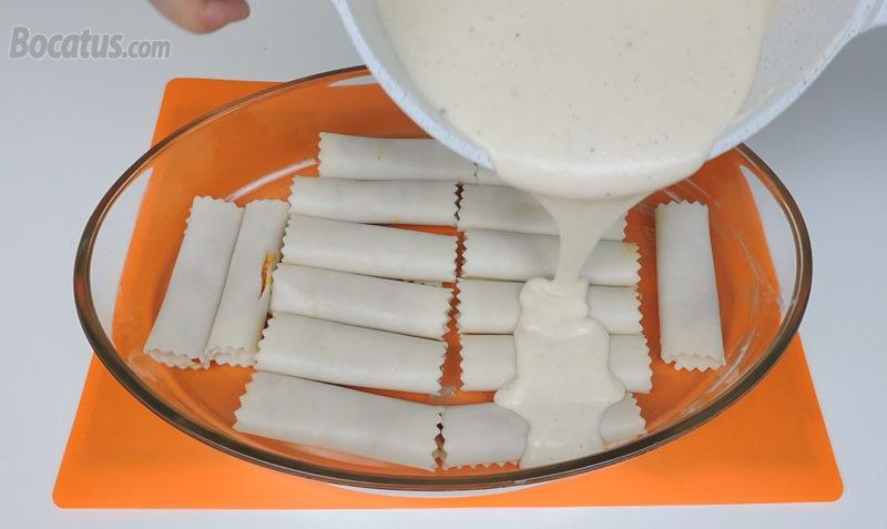 Cubriendo los canelones con la salsa bechamel