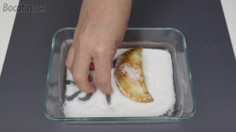 Rebozando las empanadillas en azúcar y canela