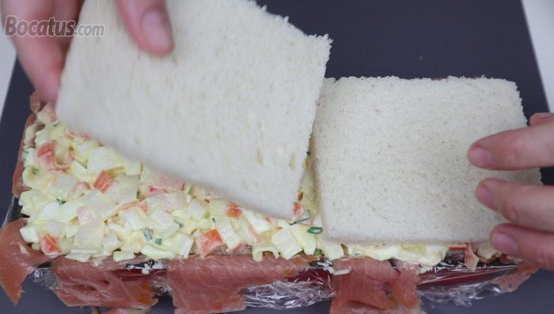 Colocando la última capa de pan sobre el relleno de surimi y huevo