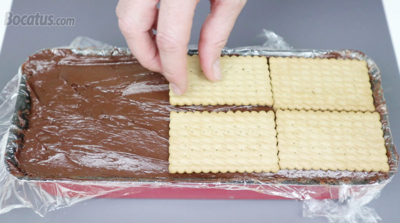 Colocando la última capa de galletas sobre la crema de chocolate negro
