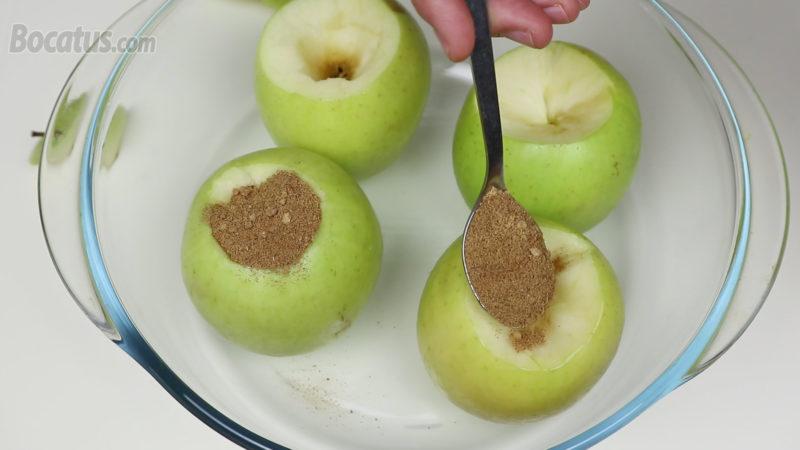 Repartiendo la mezcla de panela y canela dentro de las manzanas