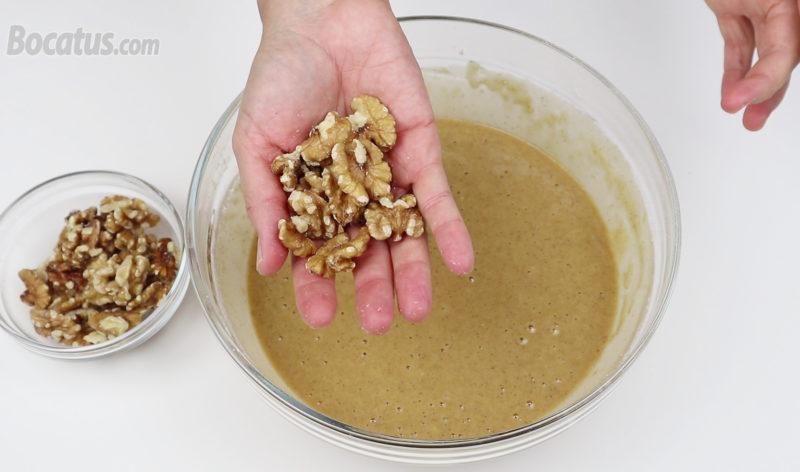 Añadiendo un puñadito de nueces a la masa del bizcocho